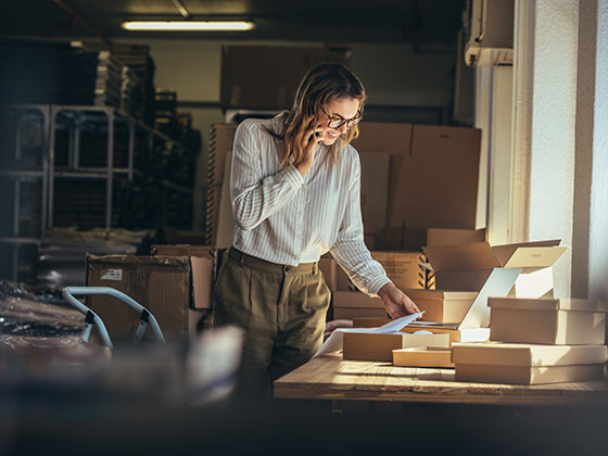 Photo of business owner processing e-commerce orders. A 30 something blond white woman wearing white blouse and tan trousers who is on the phone, processing the many package orders on the table in front of them.