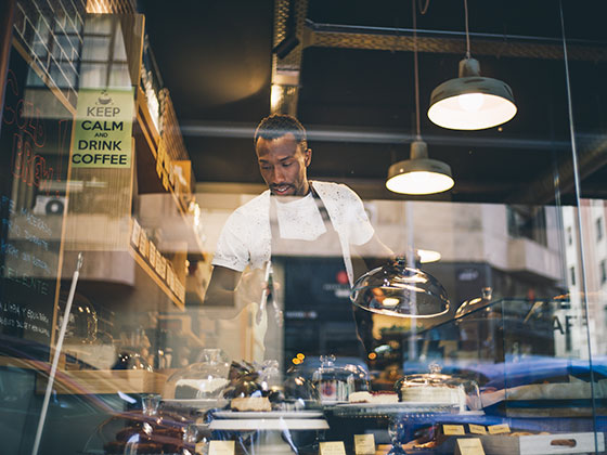 A baker putting cakes in the window of the bakery. The baker is a 40 something black man wearing a white t-shirt and black apron.